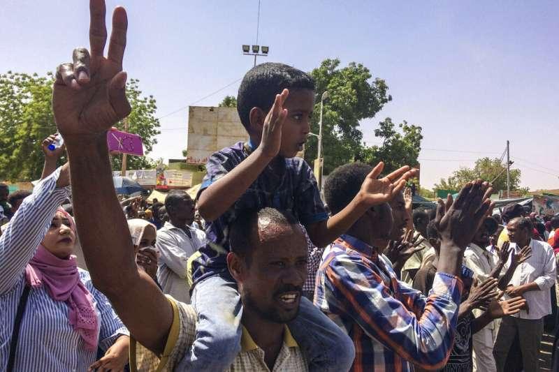 蘇丹首都喀土穆的民眾9日在軍方總部附近聚眾抗議,呼籲巴希爾總統下台。(美聯社)