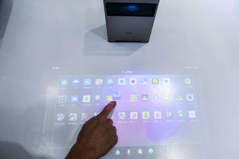 第七屆中國電子資訊博覽會(CITE2019)在深圳會展中心開幕。觀眾在海爾展台體驗桌面投影互動系統。(新華社)