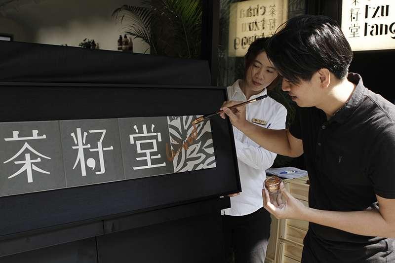 開幕記者會實況_茶籽堂創辦人趙文豪在開幕儀式上進行窯燒匾額簽名(圖/茶籽堂)