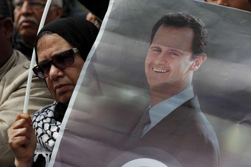 2019年月,敘利亞總統阿塞德的支持者拿著他的海報,抗議阿拉伯國家聯盟凍結國代表權。(美聯社)