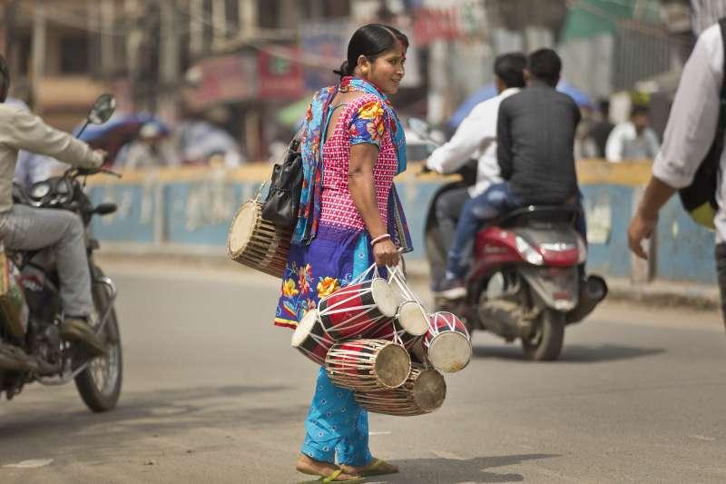 印度街頭一名女性手拿印度傳統的樂鼓,在街上販售。(美聯社)
