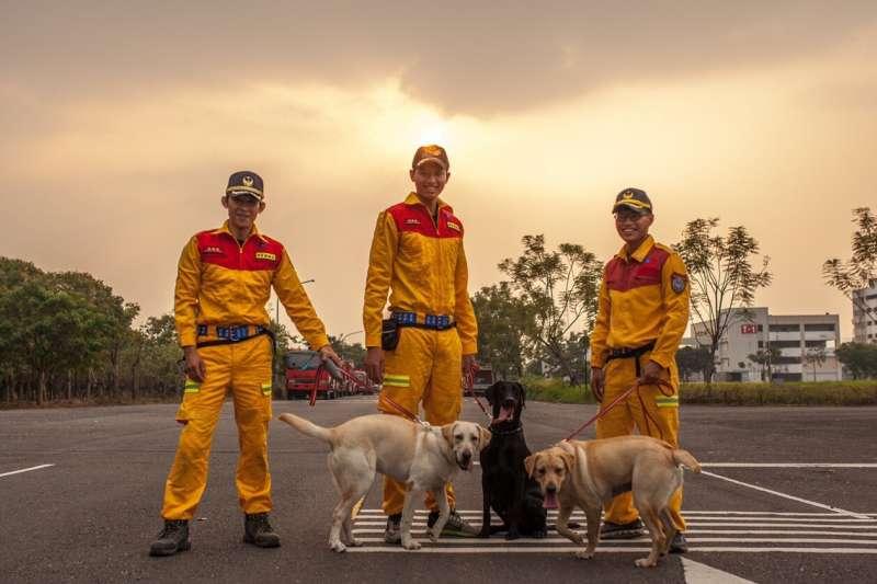 新竹市消防局特種搜救隊去年派3名隊員前往內政部消防署訓練中心,與搜救犬一對一進行培訓,其中2隻通過初試的搜救犬,將於25日新竹市民安5號演習時亮相。圖為領犬員與搜救犬合照。(新竹市政府提供)