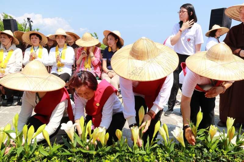 世界地球日,新北宗教團體信眾將百合花依序置放舞台前。(圖/靈鷲山佛教教團提供)