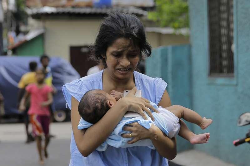 22日下午,聖安東尼教堂附近一輛貨車上發現有爆裂物,一名母親抱著嬰兒驚慌逃走(美聯社)