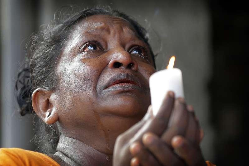 4月23日,一名信奉天主教的斯里蘭卡婦女流淚向罹難者致哀並祈禱(美聯社)