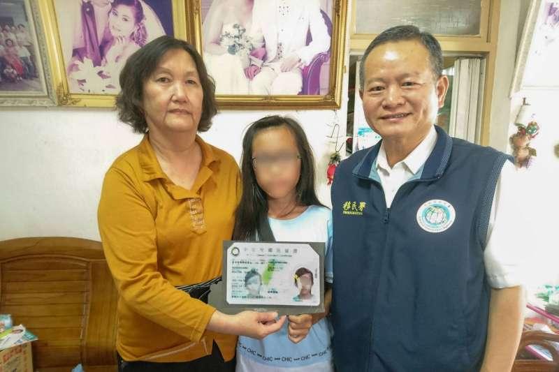 移民署嘉義縣服務站主任林炳煌(右)透過行動列車到府親送台灣地區居留證給張桂英(左)和無國籍女童恩恩(中)母女。(移民署提供)