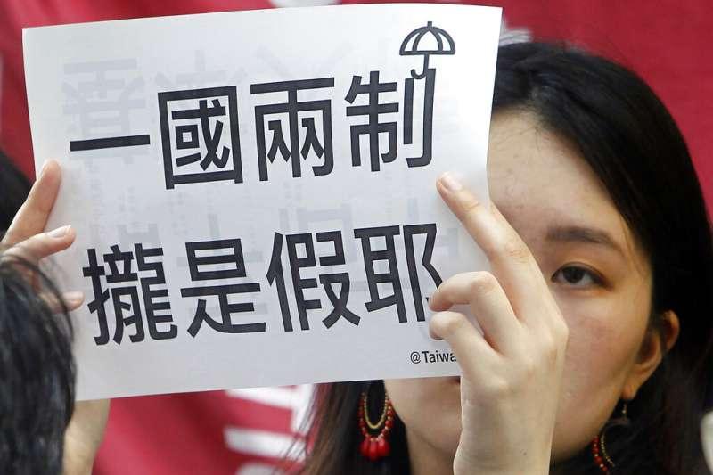 佔中九子案24日宣判刑期,聲援者也在台灣抗議示威,高舉「一國兩制攏是假」。(美聯社)