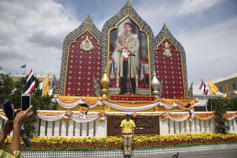 2019年5月4日,泰國國王「拉瑪十世」瓦吉拉隆功加冕儀式,民眾站在他的照片前。(美聯社)