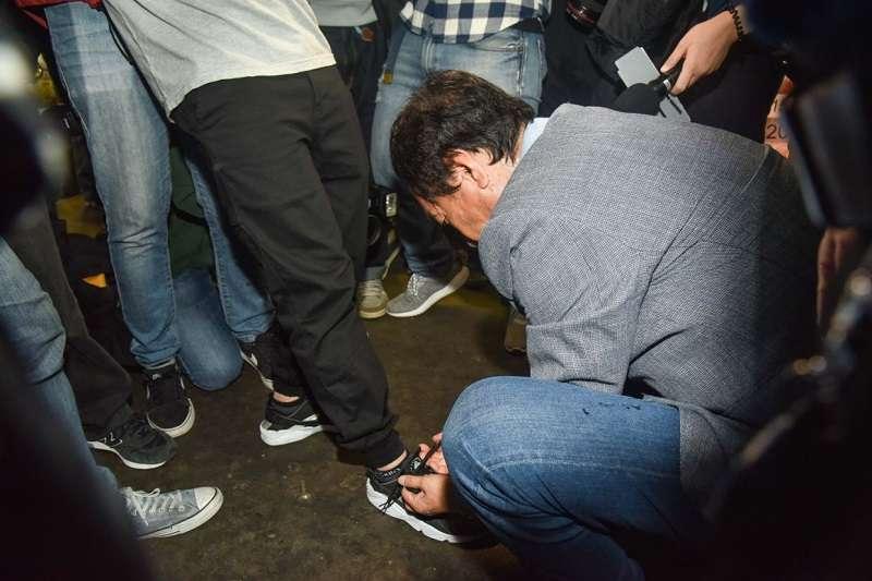 20190509-今(9)日參加國民黨總統初選的鴻海董事長郭台銘出訪內湖花市,見隨行記者鞋帶掉了,便蹲下身親自為其繫上鞋帶,展現親和的一面。(翻攝自YouTube)