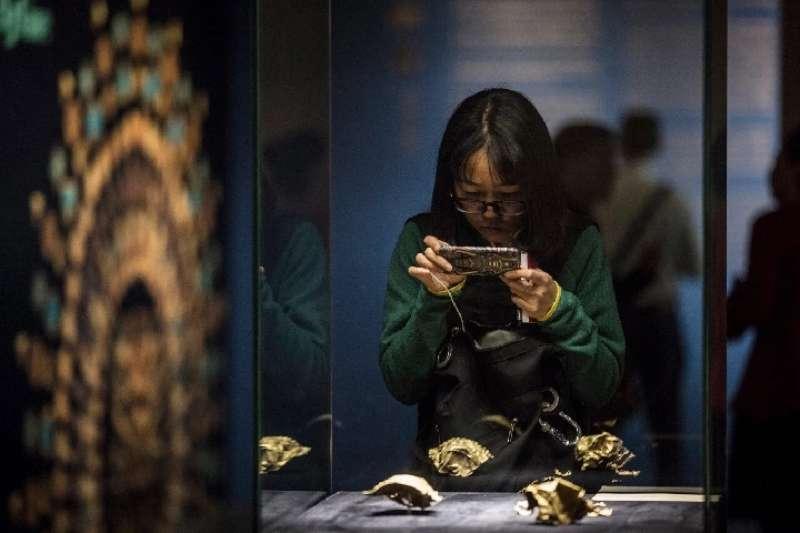 一名觀眾在清華大學藝術博物館欣賞來自阿富汗的文物。(新華社)