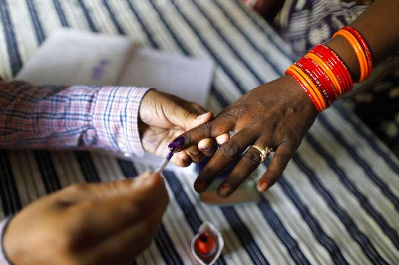 印度今年4月到5月舉行長達39天的國會大選,選務人員在一位女性選民的手指塗上墨水,準備進行投票。(美聯社)