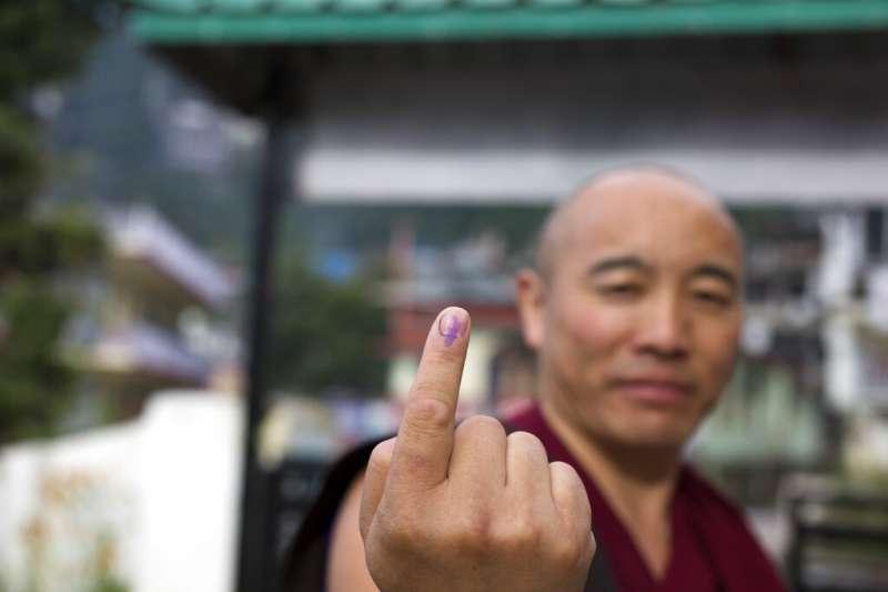 印度有高達9億選民參與今年4到5月間的投票,一位藏傳佛教的喇嘛向媒體展示沾了墨水的手指。(美聯社)