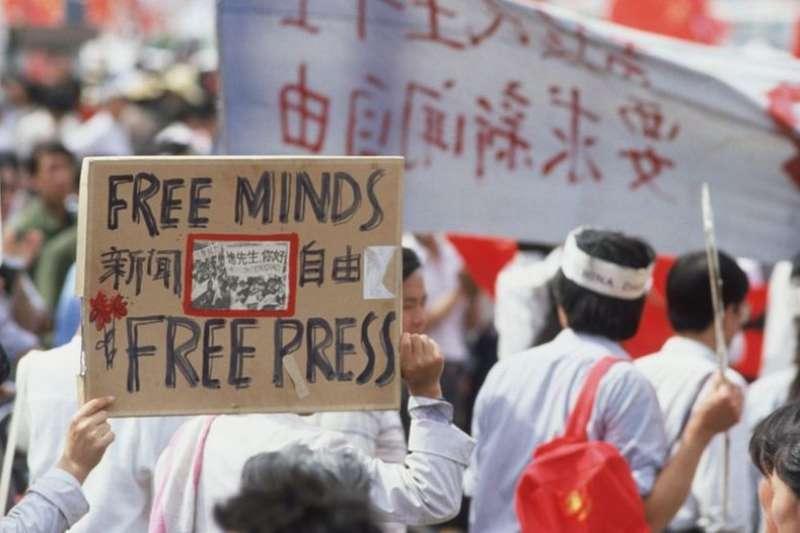 天安門廣場前高舉新聞自由標語的抗議民眾。(BBC中文網)