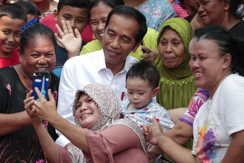 印尼總統佐科威在宣布勝選後,與支持者一同自拍。(美聯社)