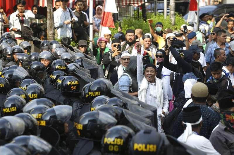 印尼總統佐科威21日宣布勝選,但普拉伯沃的支持者在選委會外聚眾抗議,大批鎮暴警察嚴陣以待。(美聯社)