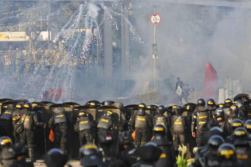 印尼總統佐科威21日宣布勝選,但普拉伯沃的支持者22日凌晨繼續抗議,鎮暴警察則發射催淚彈希望驅散人群。(美聯社)