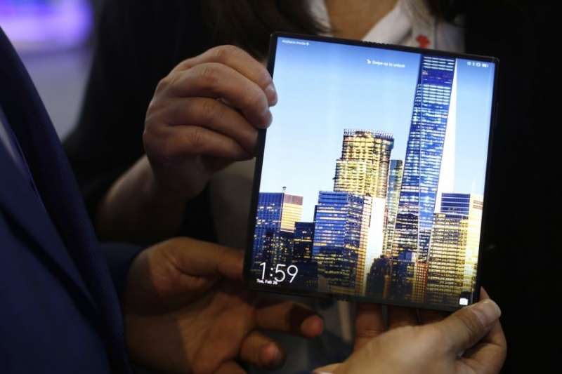 一位男士在巴賽隆納世界移動大會上拿著一部華為Mate X可折疊5G智慧型手機。(美聯社)