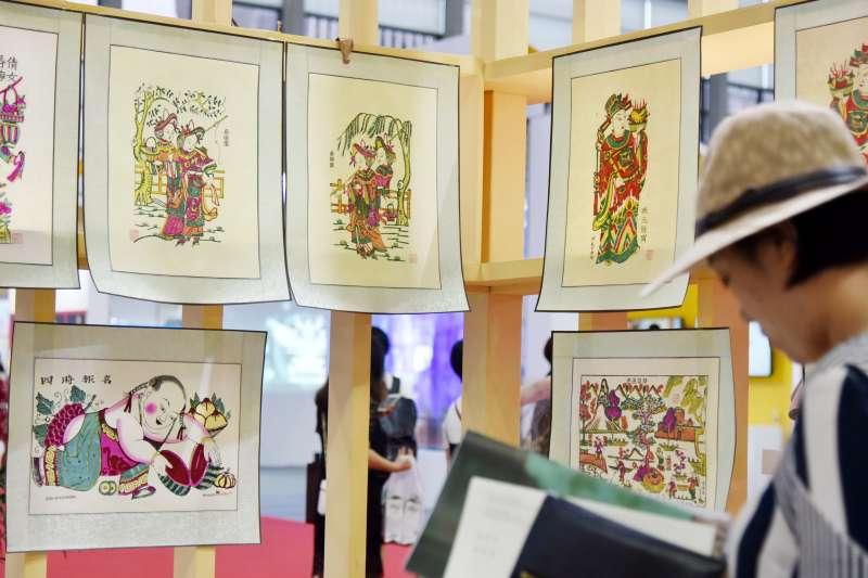 參觀者在文博會非遺展館欣賞陝西鳳翔木版年畫。(新華社)