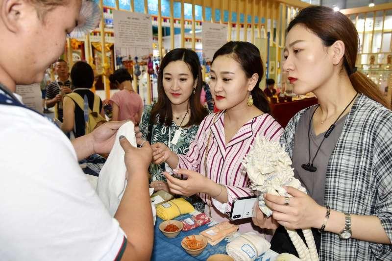 幾名參觀者在文博會非遺展館欣賞白族紮染技藝。(新華社)