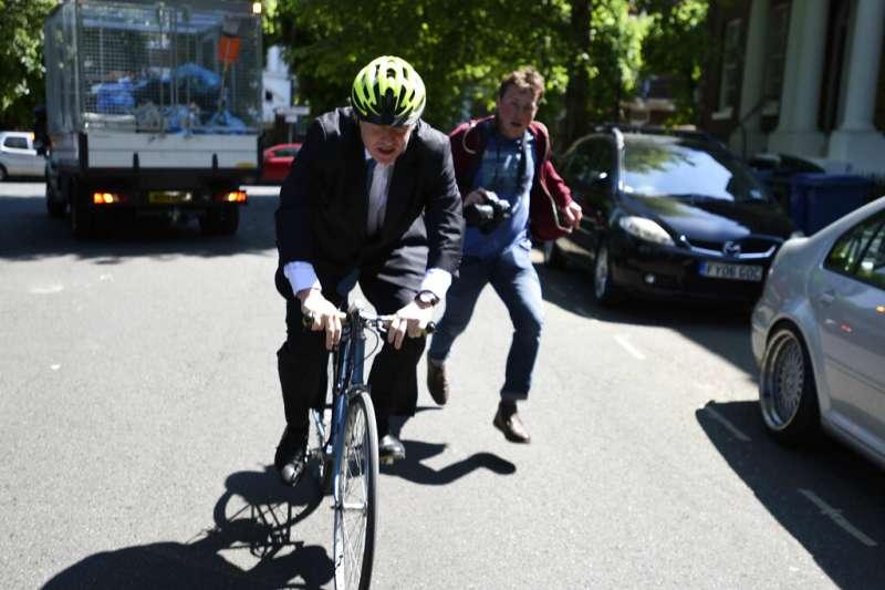 英國首相梅伊5月24日宣布將於2019年6月7日辭職,前外相強森(Boris Johnson)是熱門繼任人選,強森騎自行車離家,甩掉後方欲拍攝的記者。(AP)