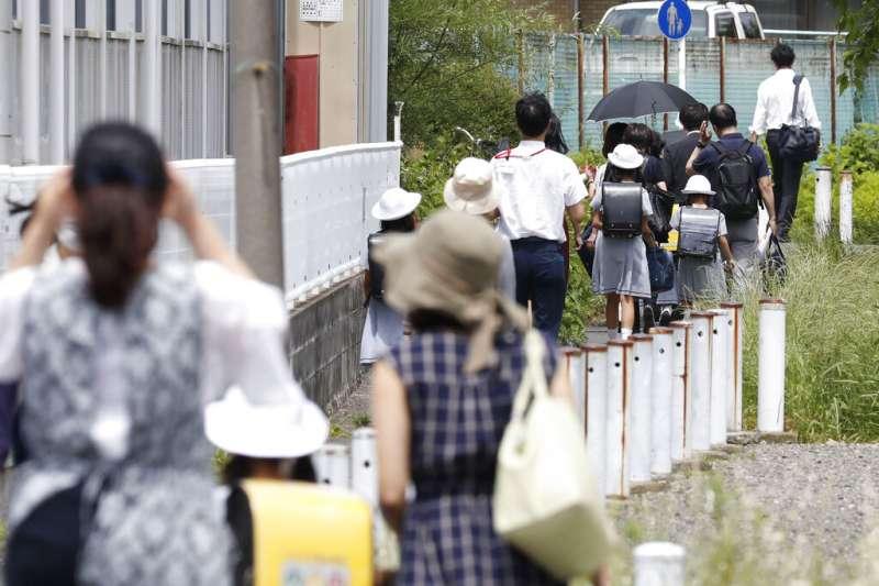 川崎市28日傳出無差別殺人案,當地家長紛紛接送自家孩子上下學。(美聯社)