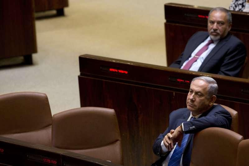 以色列國會29日晚間投票通過解散國會,納坦雅胡(前排)與昔日盟友利伯曼(後排)鬧翻,互相指責。(美聯社)