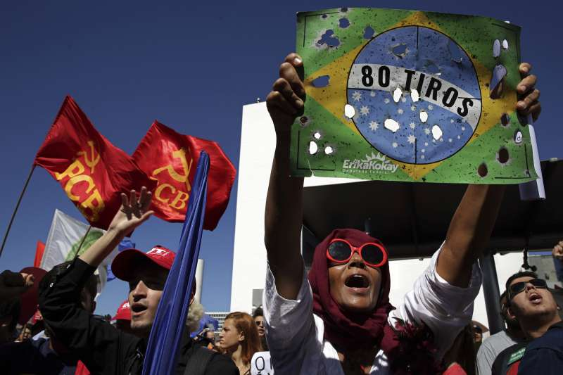 學生舉起破碎的巴西國旗,抗議政府亂刪高教經費。(AP)