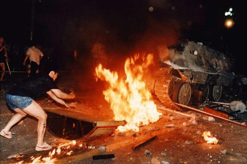 六四、1989年6月4日,北京街頭示威學生在燃燒的路障前試圖阻止坦克前進。(AP)