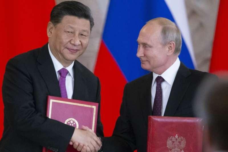 2019年6月5日俄羅斯總統普京和中國國家主席習近平在俄羅斯莫斯科克里姆林宮舉行會談後的簽字儀式上交換文件(AP)