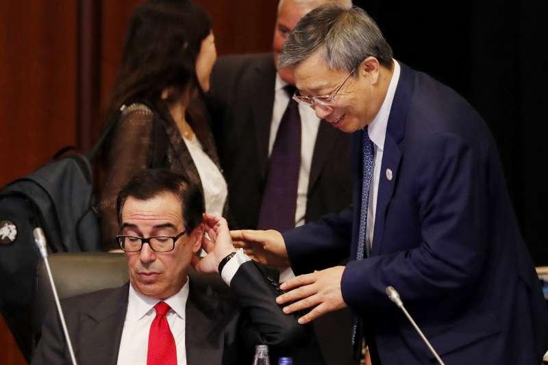 2019年6月8日,美國財政部長馬努欽(左)與中國人民銀行行長易綱在福岡的G20財長會議上交談(AP)