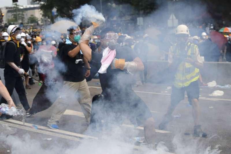 香港的「反送中」爭議12日在金鐘街頭上演流血衝突,一名示威者撿起催淚彈準備擲回警方陣營。(美聯社)
