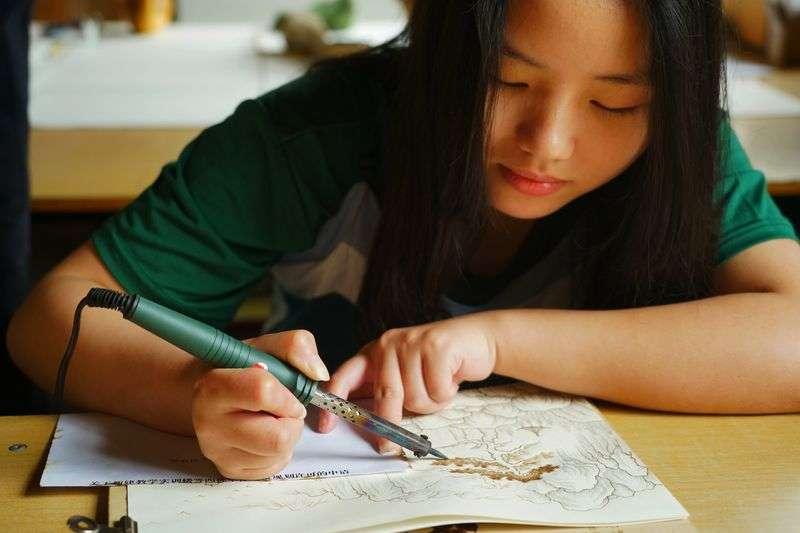 學生成亞萍練習烙畫技藝。(新華社)