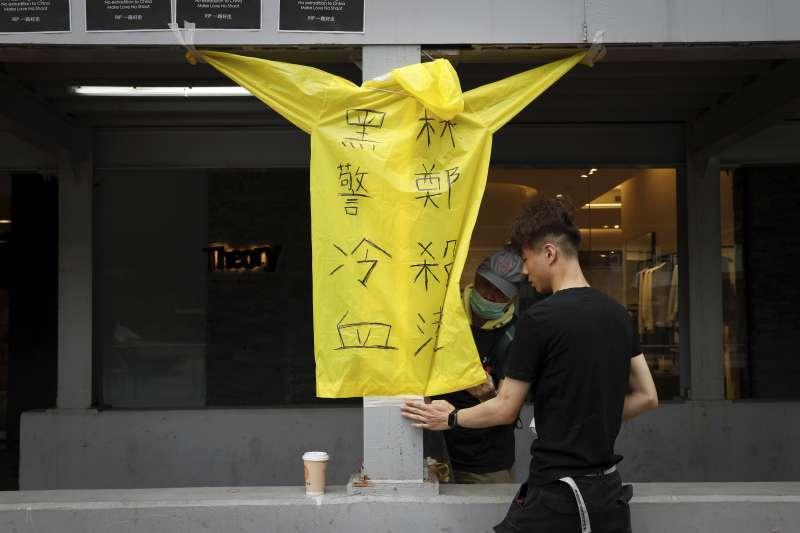 2019年6月15日,一名反送中示威者在金鐘太古廣場懸掛橫幅,要求香港政府全面撤回《逃犯條例》,不幸墜樓身亡,事發現場掛起一件寫著「林鄭殺港,黑警冷血」的黃色雨衣(AP)。