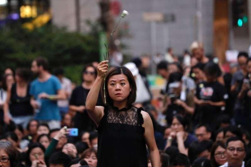 2019年6月14日,一名女子手持鮮花,與數百名母親一起抗議《逃犯條例》修法。(美聯社)