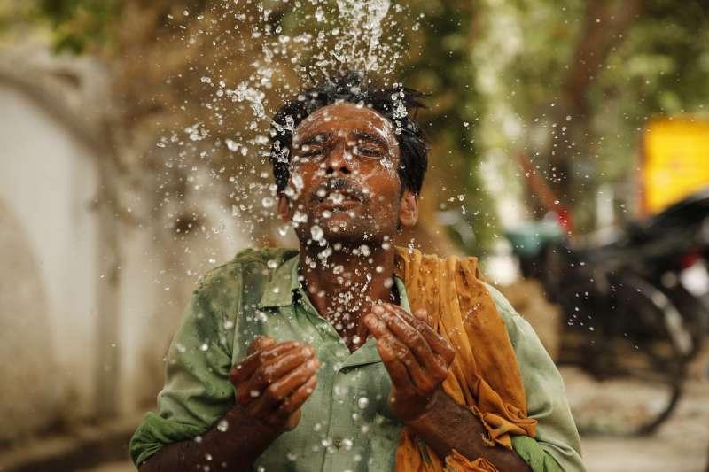 6月13日,印度北方邦安拉阿巴德,一名勞工往臉上潑水降溫(美聯社)