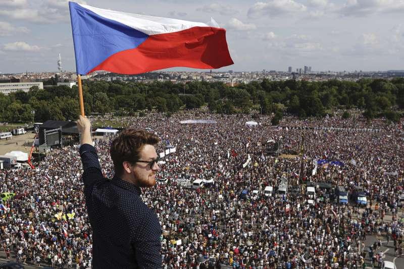 6月23日,多達25萬人走上捷克布拉格街頭抗議,要求捷克總理巴比什下台,一名男子舉著捷克國旗(美聯社)