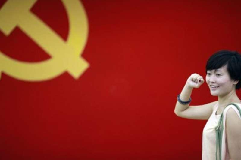 在上海的中共第一次代表大會會址,一名女子在中國共產黨黨旗下擺出宣誓姿勢。(資料照,美聯社)