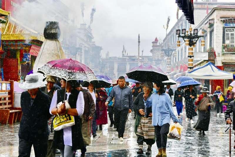 近日拉薩連續「高溫」,7月3日,一場降雨給市民送來些許清涼,圖為八廓街上的人們在雨中漫步。(新華社)
