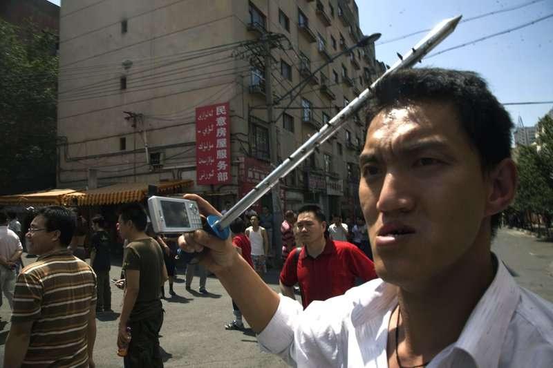 在七五事件中,有漢人男子被拍到持帶刺鐵棍加入對維吾爾人的復仇行動中。(AP)