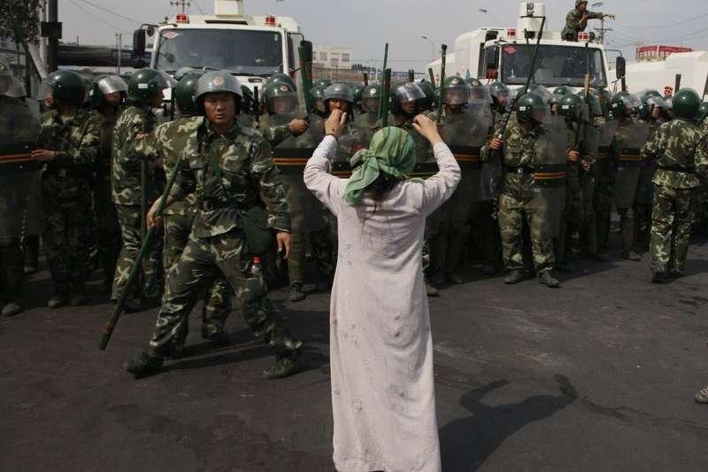 圖為七五事件後兩日,一名維吾爾婦女在武警面前抗議。(AP)