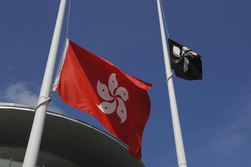 高掛22年的紅白紫荊花區旗仍未獲香港人認同,一旁為反送中示威群眾掛上的黑色紫荊花旗(AP)