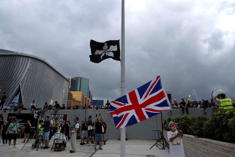 香港「反送中」民眾升起染黑的紫荊花香港區旗,對先前跳樓的民眾致意。(AP)