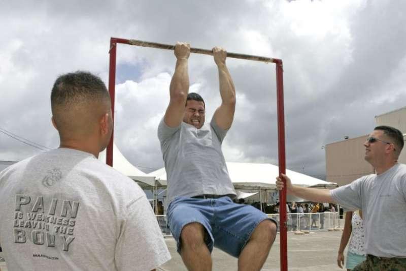 在夏威夷一處美軍基地,一名年輕人在海軍陸戰隊招兵人員的注視下參加拉單槓比賽。(美聯社)