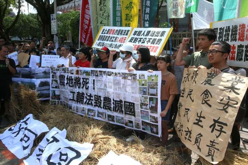 環保團體在立法院門口抗議「工輔法毀農滅國」,並丟擲成捆稻草表達不滿。(柯承惠攝)