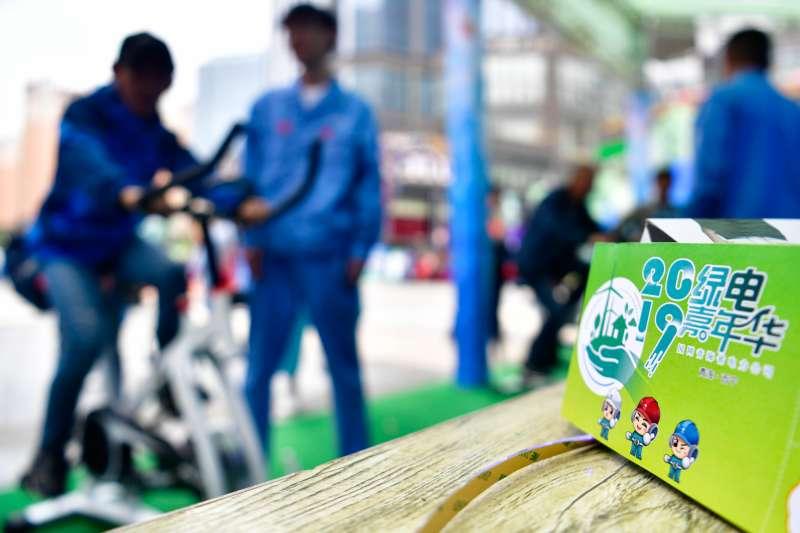 西寧市民在「綠電嘉年華」活動現場體驗騎單車發電。(新華社)