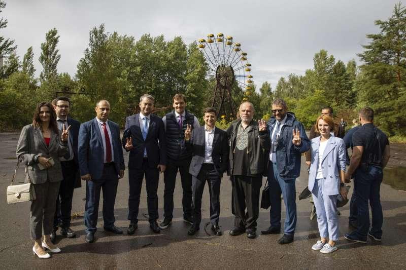 烏克蘭總統在車諾比廢城普里雅特遊樂園的摩天輪前,與官員合影。(AP)