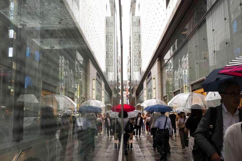 日本連日綿綿陰雨,銀座車站附近的往來行人也都撐起雨傘。(美聯社)