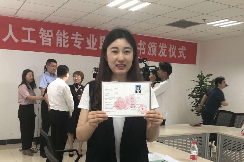 天地偉業技術有限公司研究院嵌入式四部員工劉婉琪在天津展示中國首張人工智慧專業職稱證書。(新華社)