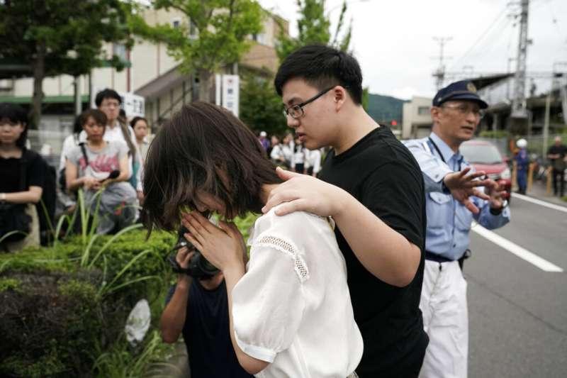京都動畫公司18日陷入火海,釀成33死35傷的慘劇,民眾在火場附近放置鮮花悼念死難者。(美聯社)