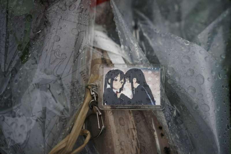 京都動畫第一工作室18日遭人縱火,釀成34死的憾事,哀悼者前往獻花,並擺上《K-ON!輕音部》周邊鑰匙環。(美聯社)